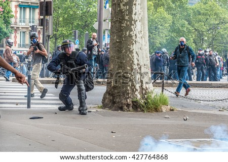 Paris, FRANCE - MAY 17, 2016 : French police, anti-riot squad, shooting tear gas against crowd to contain people during the massive protest over the labor law reforms.