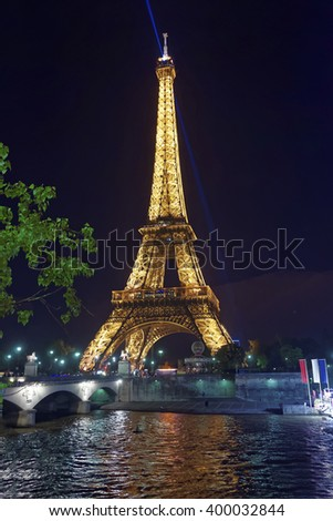 PARIS, FRANCE - MAY 3, 2012: Illuminated Eiffel Tower and Seine River in Paris in France, in the evening. Eiffel Tower is an iron lattice tower of Paris. It is a global and cultural icon for France - stock photo