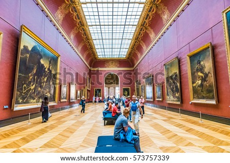 PARIS, FRANCE - MAY 25, 2016: Many people appreciate paintings in the Louvre Museum in Paris, France. The Louvre is the world's largest museum and a historic monument in Paris, France.