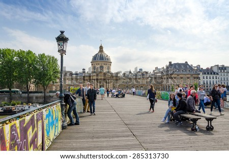 Paris, France - May 13, 2015: People visit Institut de France and the Pont des Arts or Passerelle des Arts bridge across river Seine in Paris, France. on May 13, 2015. - stock photo