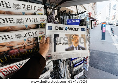 PARIS, FRANCE - MAY 9, 2017: Pov buying Die Welt newspaper front page with the picture of the newly elected French president Emmanuel Macron after the second round French Presidential election