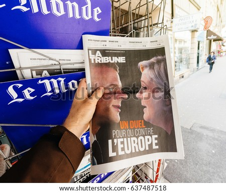 PARIS, FRANCE - MAY 9, 2017: Pov buying La Tribune newspaper front page with the picture of the newly elected French president Emmanuel Macron and Le Pen second round French Presidential election