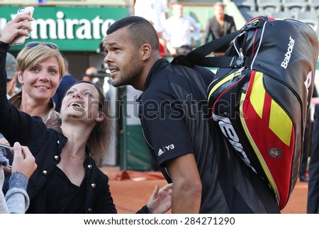 PARIS, FRANCE- MAY 24, 2015: Professional tennis player Jo-Wilfried Tsonga of France taking selfie with fans after first round match at Roland Garros 2015 in Paris, France - stock photo