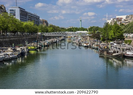 PARIS, FRANCE - MAY 18, 2014: Row of houseboats docked on Canal Saint Martin - a 4,5 km long canal, it connects canal de l'Ourcq to river Seine. - stock photo