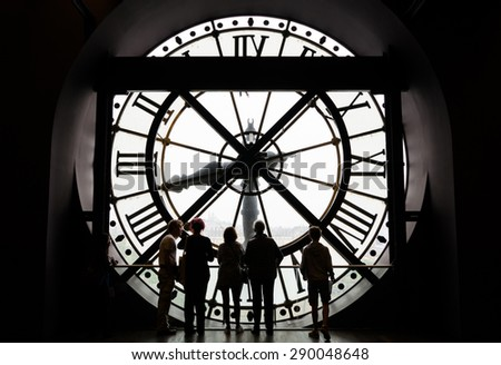 Paris, France - May 14, 2015: Silhouettes of unidentified tourists looking through the clock with roman numerals in the museum D'Orsay. The museum houses the largest collection of masterpieces. - stock photo
