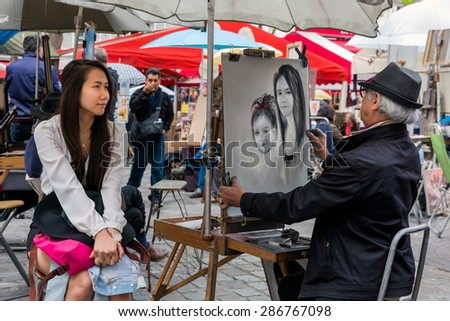 PARIS, FRANCE - May 28: Street artist is painting a beautiful woman at Place du Tertre in Montmartre, one of the most touristic attractions of the city, on May 28, 2015 in Paris, France