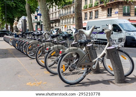 PARIS, FRANCE - May 29: Street view with unknown woman paying for renting a bicycle on May 29, 2015, Paris, France - stock photo