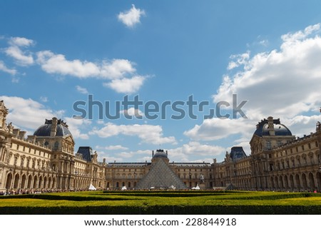 Paris, France - May 3, 2014: The famous glass pyramid at the Louvre. One of the most visited attractions in Paris. - stock photo