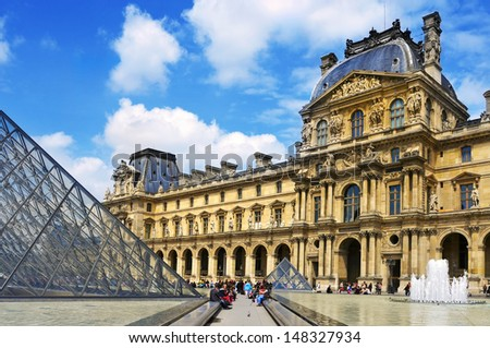 PARIS, FRANCE- MAY 17: The large glass pyramid and the main courtyard of the Louvre Museum on May 17, 2013. The Louvre Museum is one of the largest museums of the world - stock photo