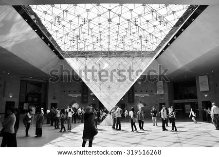 Paris, France - May 13, 2015: Tourists visit Inside the Louvres pyramid on May 13, 2015 in Paris. Louvre is one of the biggest Museum in the world, receiving more than 8 million visitors each year.  - stock photo