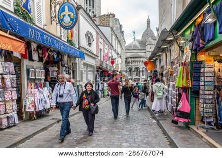 PARIS, FRANCE - May 28: Tourists walking near the gift shops of Montmartre, close to the famous Sacre Coeur Basilica on May 28, 2015, Paris, France - stock photo