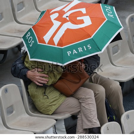 PARIS, FRANCE- MAY 31, 2015:Unidentified tennis fans under umbrella during during rainy day at Roland Garros 2015 in Paris, France - stock photo