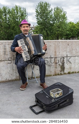 PARIS, FRANCE - MAY 29: Unknown musician playing accordion near river Seine on May 29, 2015 in Paris, France - stock photo