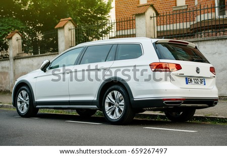 PARIS, FRANCE - MAY 28, 2017: View from below of white Volkswagen Passat Alltrack all four wheel drive car parked in city. Alltrack bridges the gap between the passenger VW range and the SUV range