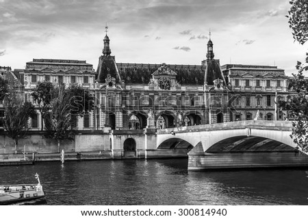 PARIS, FRANCE - MAY 30, 2015: View of famous Louvre Museum from the Seine River. Louvre Museum is one of the largest and most visited museums worldwide. Black and white. - stock photo