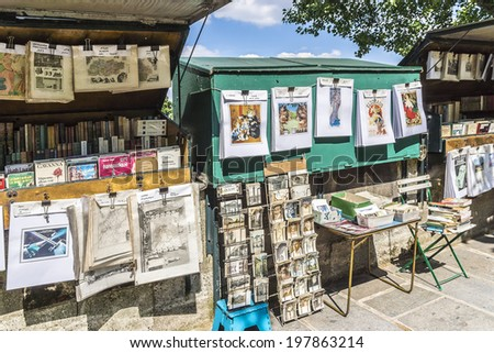 PARIS, FRANCE - MAY 18, 2014: Vintage books and pictures in open book market on embankment of river Seine near cathedral Notre Dame de. Book market on the banks of Seine is there since 16th century. - stock photo