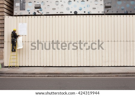 Paris, France-May 16, 2013. Workman on ladder attaches a sign to a fence on a construction site in Paris, France