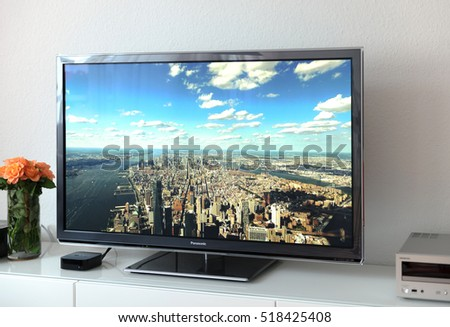 PARIS, FRANCE - NOV 21, 2015: Apple TV device next to 4k Pansonic Plasma OLED display projecting the typical Apple Screensaver of aerial city