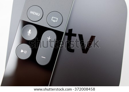 PARIS, FRANCE - NOV 10, 2015: New Apple TV media streaming  player microconsole by Apple Computers -  .  It has new touch remote swipe-to-select with integrated Siri and motion sensor  - stock photo