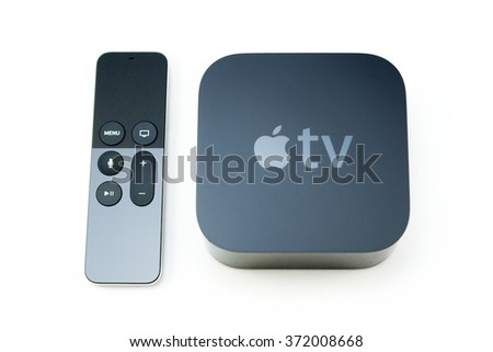 PARIS, FRANCE - NOV 10, 2015: New Apple TV media streaming  player microconsole by Apple Computers next to the new touch remote swipe-to-select with integrated Siri and motion sensor on white  - stock photo