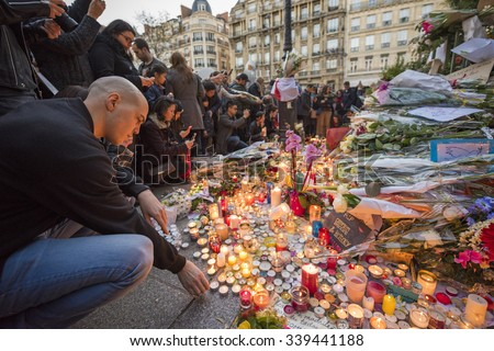 PARIS, FRANCE - NOVEMBER 15, 2015 :  A man lights a candle in front of the theater Le Bataclan in tribute to victims of the Nov. 13, 2015 terrorist attack in Paris at the Bataclan. - stock photo