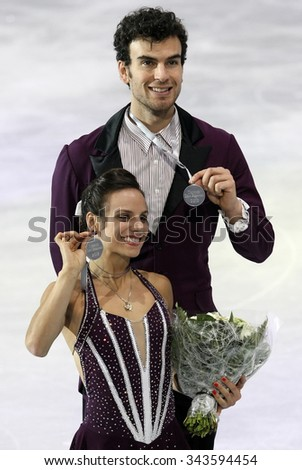 PARIS, FRANCE - NOVEMBER 16, 2013: Meagan DUHAMEL / Eric RADFORD of Canada pose after winning silver medals during the victory ceremony at Trophee Bompard ISU Grand Prix at Palais Omnisports de Bercy. - stock photo