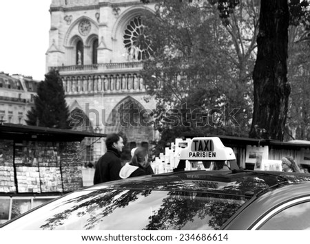 PARIS, FRANCE - NOVEMBER 30, 2013: Parisian taxi passing beside bouquiniste stands locating nearby the Notre Dame cathedral. Selling books on the banks of Seine river began around the 16th century. - stock photo