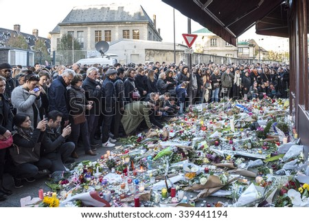 PARIS, FRANCE - NOVEMBER 14, 2015 :  People in front of the Bar Hotel Le Carillon street Alliber in tribute to victims of the Nov. 13, 2015 terrorist attack in Paris at the Bataclan. - stock photo