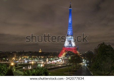 PARIS, FRANCE - NOVEMBER 21, 2015 :  The Eiffel Tower in national colors of France to prove that Paris is still standing after the terrorist attack of November 13, 2015.  - stock photo