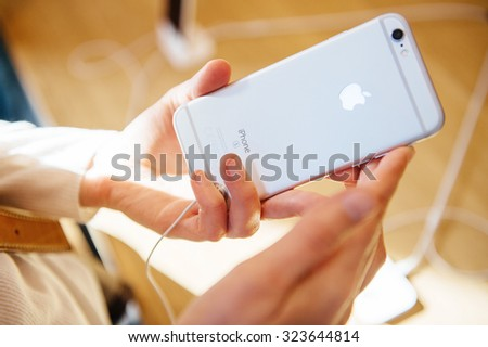 PARIS, FRANCE - OCT 3, 2015: Customer checks the back of the new iPhone 6s displayed at the Apple Store Opera - stock photo