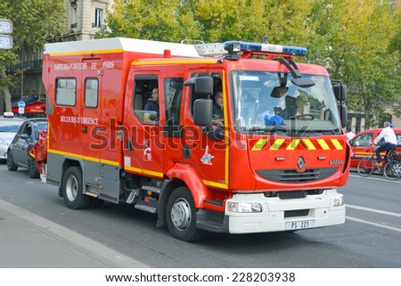 PARIS, FRANCE OCTOBER 16: Fire Truck on the street of Paris downtown on october 16, 2014. The Paris Fire Brigade , is a French Army unit which serves as the fire service for Paris. - stock photo