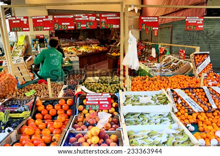 PARIS, FRANCE - OCTOBER 18 : Market fruit stall at Mouffetard street in Paris with fruits for sale on the foreground and vendor on the background on October 18th, 2013 - stock photo