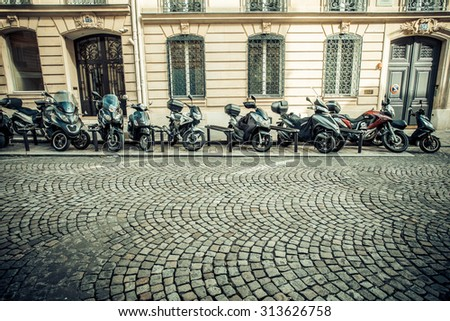 PARIS, FRANCE - OCTOBER 9, 2014:  Street scene in Paris with cobblestone and motorbikes parked.  - stock photo
