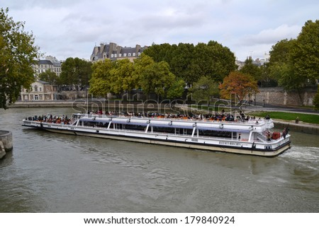 PARIS, FRANCE - OCTOBER 20: Tourist Boat in Paris, France on October 20, 2013. In paris there are several boat tourist trips across the Seine to show tourists the sights of interest.