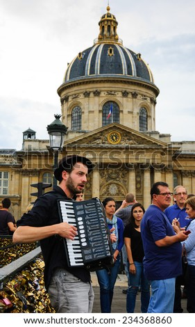PARIS, FRANCE - OCTOBER 4, 2014: Unidentified young musician plays accordion on Love Locks bridge and Academy of Fine Arts at backgrounds. Dozens buskers perform on the streets and in metro of Paris. - stock photo