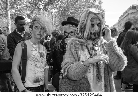 PARIS, FRANCE - OCTOBER 3, 2015: Zombie participant making call phone home or to friends with his mobile phone during Zombie parade at Place de la Republique. Zombie Walk is an annual event in Paris. - stock photo