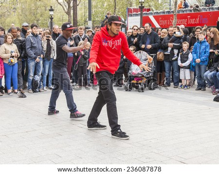 Paris, France, on May 1, 2013. Tourists see a performance of street acrobats on the Champs Elysee - stock photo