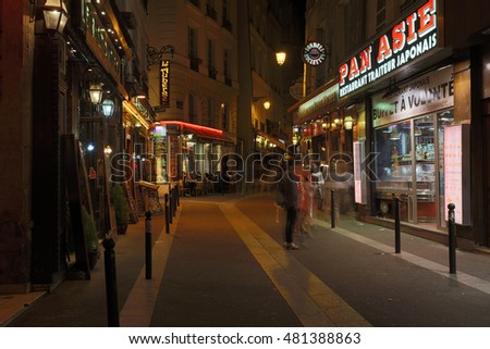 PARIS, FRANCE - 13RD AUGUST 2016: A view down a street in Paris at night showing the blurred motion of people and restaurants, cafes and other shops