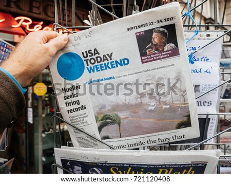 PARIS, FRANCE - SEP 23, 2017: Man buying latest newspaper USA TODAY with Hurricane Maria breaking news and picture of damages wind sea water