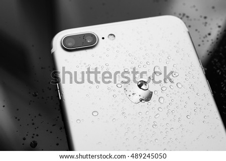 PARIS, FRANCE - SEP 26, 2016: New Apple iPhone 7 Plus unboxing and testing - water drops on rear - studio shot. New iPhone7 is one of the best waterproof smart phone in the world