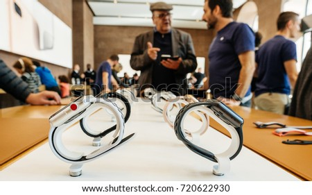 PARIS, FRANCE - SEP 22, 2017: New Apple Watch Series 3 goes on sale in Apple Store with Apple Genius Explaining to customer about Watch advantages - multiple wathces in a row