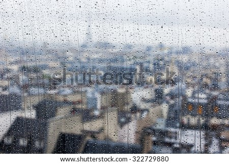 PARIS, FRANCE, SEPTEMBER 27, 2015. A view of the city from a window from a high point during a rain. Rain drops on glass. Focus on drops - stock photo