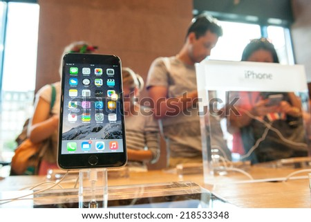 PARIS, FRANCE - SEPTEMBER 20, 2014: An iPhone 6 smartphone stands on display inside an Apple Store with lots of customer behind admiring other iPhone 6 - stock photo