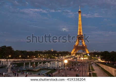 PARIS, FRANCE - SEPTEMBER 10: Artificially illuminated Eiffel tower with the rising moon in the background. Many people enjoyed the view to the Eiffel tower on September 10, 2011 in Paris, France. - stock photo