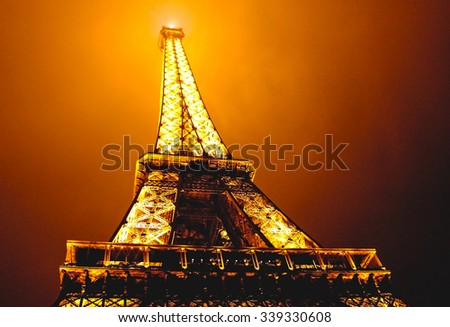 PARIS, FRANCE- SEPTEMBER 14, 2013: Eiffel tower in the dark misty night and warm orange light. Eiffel tower is the most famous tourist attraction in Paris. (HDR effect) - stock photo