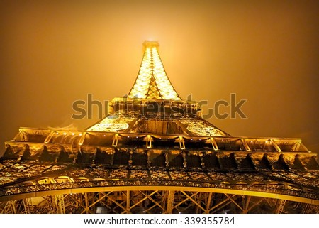 PARIS, FRANCE- SEPTEMBER 14, 2013: Eiffel tower in the dark misty night and warm orange light. Eiffel tower is the most famous tourist attraction in Paris. (filter, vignette effect) - stock photo