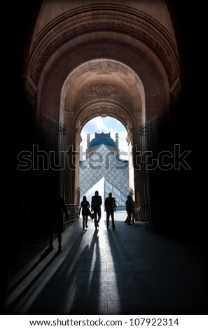 PARIS, FRANCE - 5 SEPTEMBER 2011: Louvre pyramid with silhouettes of people in foreground. Most visited art museum in the world and a historic monument. Nearly 35000 art objects. Sept 5, 2011 Paris. - stock photo