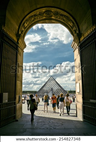 PARIS, FRANCE - 8 SEPTEMBER 2013: Louvre pyramid with silhouettes of people in foreground. Most visited art museum in the world and a historic monument. Nearly 35000 art objects. Sept 8, 2013 Paris. - stock photo