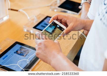 PARIS, FRANCE - SEPTEMBER 20, 2014: Man taking photograph with the new iPhone 6 during the sales launch at the Apple Inc. store in Paris, France - stock photo