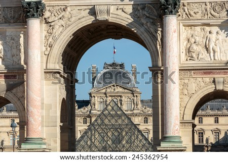 Paris, France - September 9, 2014: Paris - Triumphal Arch and Glass Pyramid in Louvre. Louvre is one of the biggest Museum in the world; receiving more than 8 million visitors each year. Paris, France - stock photo